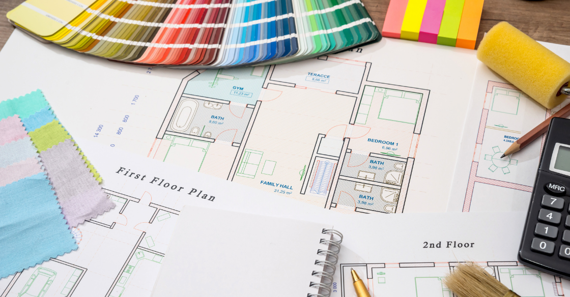 Interior design drawings and paint samples laid out on a table