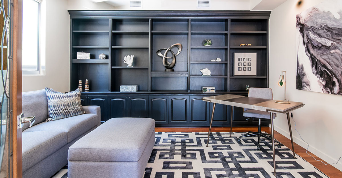 Home office with black bookcase and gray couch